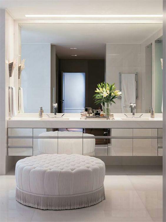 Một bức tường gương, tủ đôi và viên đá cẩm thạch trắng trên tường và trên sàn nhà
