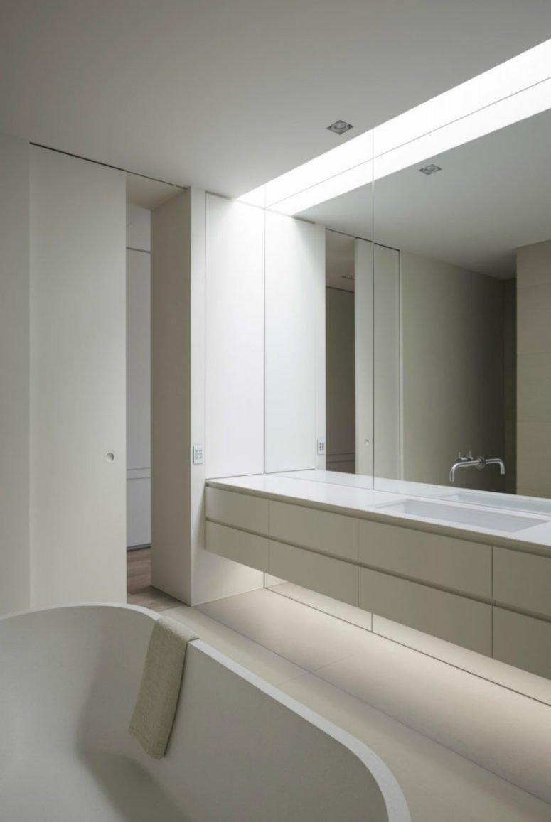 Phòng tắm nhỏ gọn trong màu trắng và một bức tường gương hư ảo
