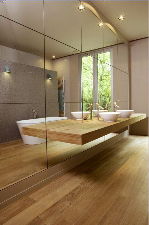 Phòng tắm nhỏ gọn với gỗ màu nhạt và một bức tường gương