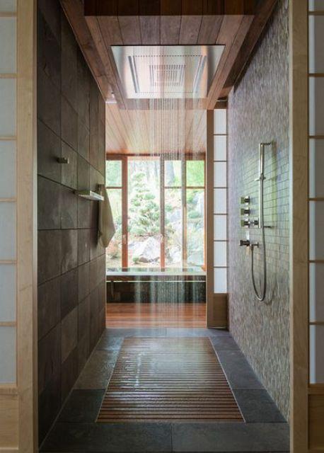 Phòng tắm theo kiểu Nhật Bản với gam màu tối, có vòi hoa sen và sàn gỗ