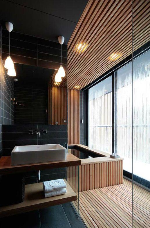 Khu vực tắm gợi cảm với gạch ốp lát màu đen và các tấm gỗ nhẹ giữ cho không gian nhỏ gọn nhưng rất sang trọng