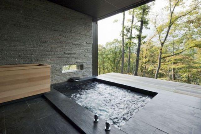 Gạch đen và việc sử dụng đá trong không gian tắm trong nhà ngoài trời cho nó một cái nhìn tối thiểu Nhật Bản