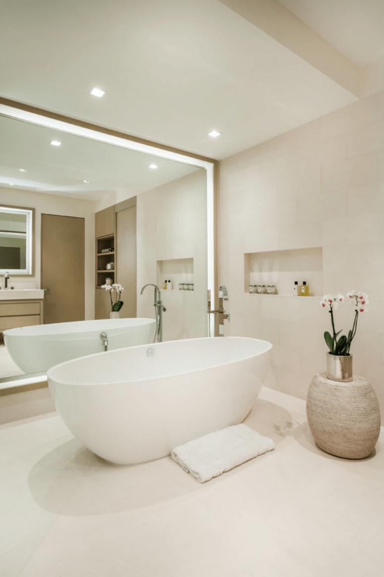Ánh sáng lên tường gương bên cạnh bồn tắm mang đến cho phòng tắm cảm giác như ở trong khách sạn